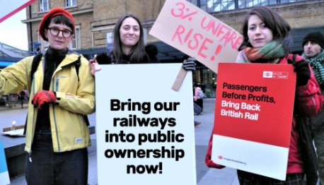 "Three protesters outside Kings Cross station, with a placard reading ""Bring our railways into public ownership now!"""