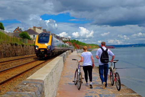 Walking with bikes by a train