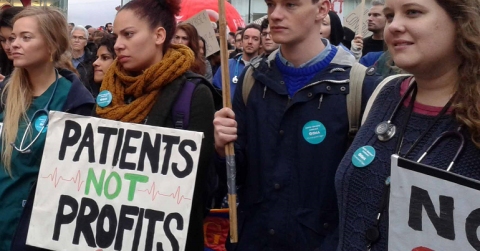 "Protest with placard reading ""patients not profits"""