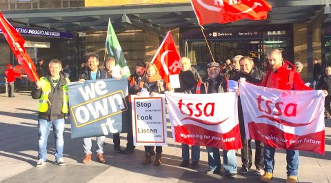 campaigners outside Kings Cross holding flags, banners and the stop look listen placard
