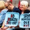 """A group of protesters with signs reading """"No health sell off"""" and """"stop privatising our NHS"""""""