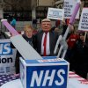 An image of a protester dressed as Donald Trump, carving up a box labelled 'NHS' outside Parliament, London