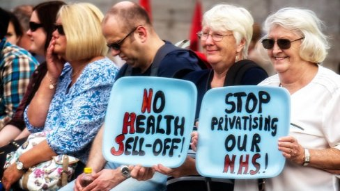 "A group of protesters with signs reading ""No health sell off"" and ""stop privatising our NHS"""