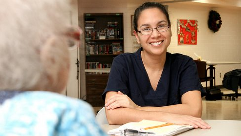 Photo of care assistant talking to older person