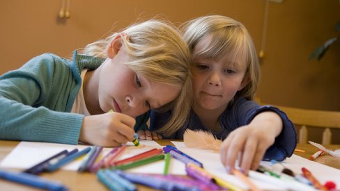 Photo of children drawing with crayons