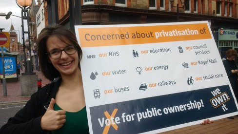 Ellen from the We Own It team with a public ownership poster