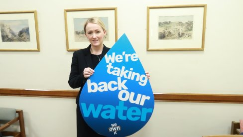 Rebecca Long-Bailey holding a placard in the shape of a water drop which reads: 'Let's take back our water'